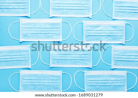 Medical hygienic mask, Face protective masks on blue background.Disposable surgical face mask protective against Coronovirus Covid-19,pollution, virus, flu.Healthcare medical surgical Flat lay pattern #1689031279