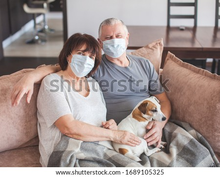 Coronavirus CoVid-19 Couple old aged senior people at home with seasonal winter cold illness disease sit down on the sofa. Elderly couple in medical masks during the pandemic #1689105325