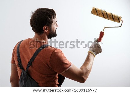Painter working. Home renovation concept. Skillful and professional painter. Wall painting tool. Brush roller painter. Confident painter worker man. Man with paint roller over white wall. #1689116977