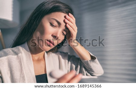 Coronavirus fever Asian woman touching forehead checking temperature with thermometer. COVID-19 symptoms include, fever, cough, respiratory breathing difficulty, in more severe cases, pneumonia. Royalty-Free Stock Photo #1689145366