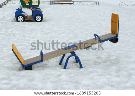 Children's swing for two on the playground against the background of winter snowdrifts. Concept of children's entertainment and street games. Stock photo for web and print with empty space for text.