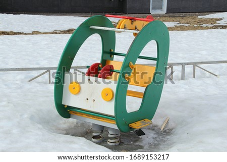 Children's swing in the form of a car on the playground against the background of winter snowdrifts. Concept of children's entertainment and street games. Stock photo for web and print with empty