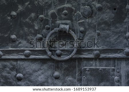 Detailed view ov a very old and dark church door with rivets and a circular knocker handle #1689153937