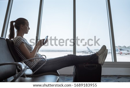 Young woman sitting using her smartphone waiting to board her flight at airport terminal. Royalty-Free Stock Photo #1689183955