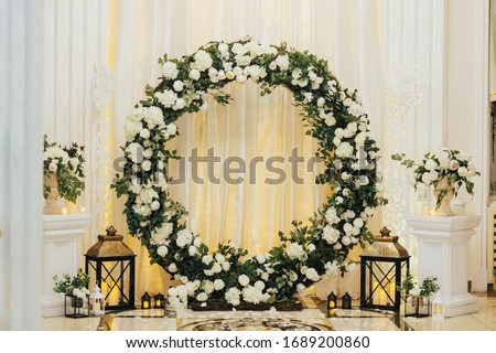 Wedding arch at the restaurant. Round flower arch. Trend in the wedding banquet room is a white  arch decorated with flowers and greens, in the background white cloth. Royalty-Free Stock Photo #1689200860
