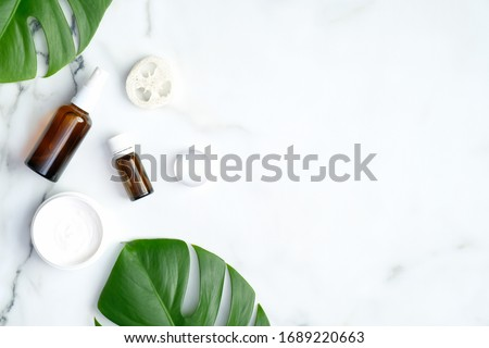 SPA natural organic cosmetic products with monstera tropical plant leaves on marble background. Flat lay, top view, copy space. Skin care and beauty treatment concept Royalty-Free Stock Photo #1689220663