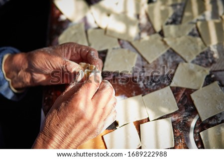 Woman's hands makes a vareniki in front of sunbeams. Ukrainian dish. Black and white #1689222988