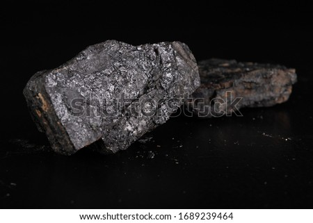 Lignite lump. Carbon as an energy source. Dark background. #1689239464