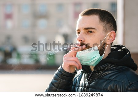 Coronavirus. Smoking. Closeup man with mask during COVID-19 pandemic smoking a cigarette at the street. Smoking causes lung cancer and other diseases. The dangers and harm of smoking. #1689249874