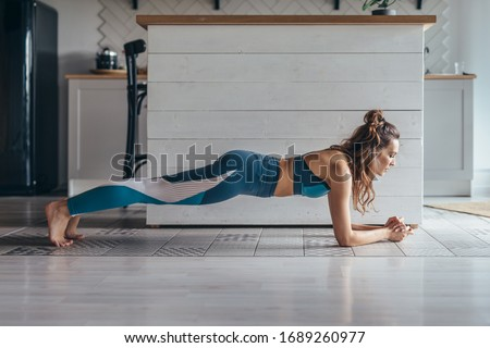 Fit woman working on abdominal muscles doing plank exercise, core workout at home. Royalty-Free Stock Photo #1689260977