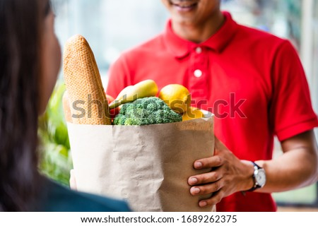 Asian deliver man worker in red color uniform handling bag of food, fruit, vegetable give to young beautiful female costumer in front of the house. Postman and express grocery delivery service concept #1689262375