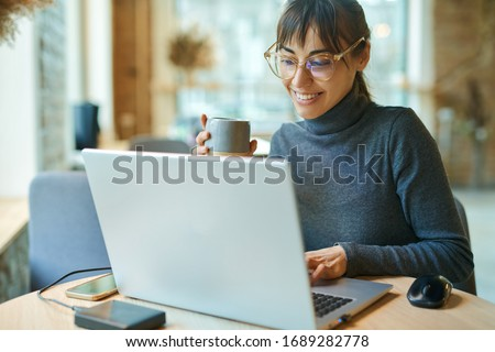 Young smiling business woman in spectacles working on portable laptop computer. Female copywriter sitting at desk and typing on keyboard, working on project, writing down ideas into netbook #1689282778