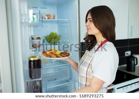 Young woman on kitchen during quarantine. Stand in front opened fridge and hold plate with fruit, citrus and cookies. Ready to cook. #1689293275