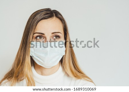 Anxious woman with face mask worried about the Covid-19 outbreak staying at home #1689310069