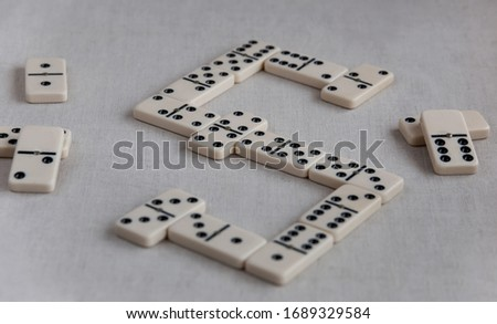Board game of dominoes - dice with dots laid out on table. Hobbies and recreation, activities at home and in quarantine. Selective focus. Close up. #1689329584