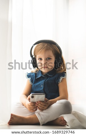 Beautiful little caucasian girl in a casual listening to the music in a headphones and watching cartoons on smartphone or phone. Baby girl use headphones and hold the phone.
