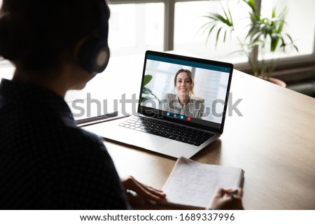 Back view of female employee sit at desk at home have Webcam conference on laptop with business partner or client, woman worker talk on video call with coworker or consultant, watch online webinar #1689337996