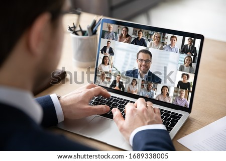 Rear view of businessman speak on web conference with diverse colleagues using laptop Webcam, male employee talk on video call with multiracial coworkers have online meeting briefing from home Royalty-Free Stock Photo #1689338005