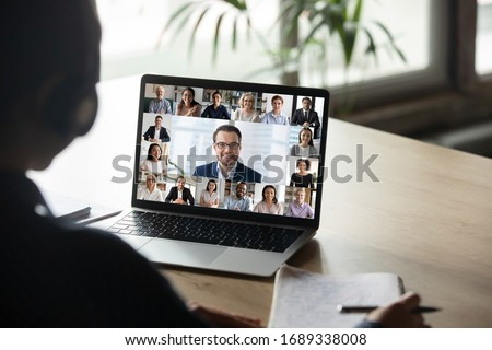 Back view of female employee engaged in team Webcam conference on laptop, have online briefing or consultation from home, woman worker speak talk on group video call with diverse colleagues Royalty-Free Stock Photo #1689338008