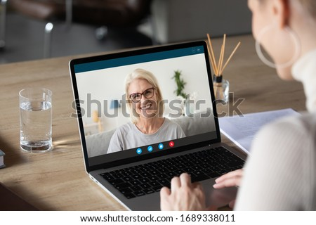 Back view of woman speak talk on video call on computer with smiling elderly mother, young female communicate online using laptop Webcam chat with happy mature mom, quarantine at home #1689338011