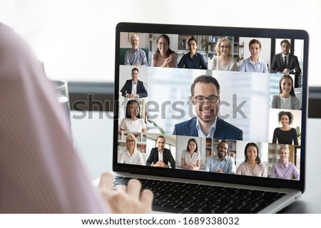Close up of employee talk on video call on laptop with diverse colleagues, worker speak on web conference with multiracial coworkers, have online briefing with team, use Webcam on computer Royalty-Free Stock Photo #1689338032