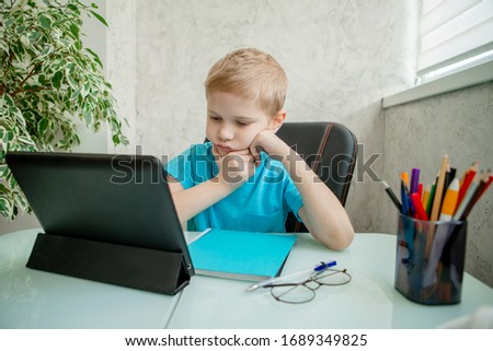 Young boy learn by tablet at home. Distance learning in quarantine. Isolation. Homework #1689349825