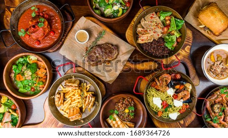 Assorted food set on table, Pasta with seafood, steak ribeye, club sandwich, turkey with black rice, salad with kinoa, tartar from beef, fried loungustine #1689364726