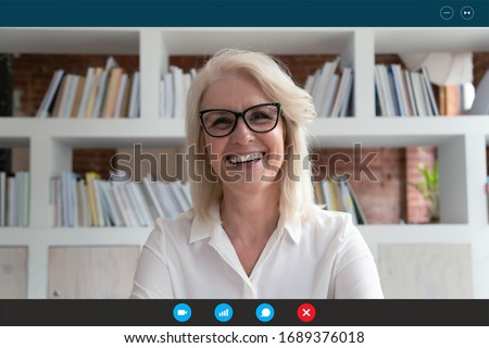 Headshot portrait screen application view of smiling elderly woman look at camera talk on video call with relatives, happy mature female go online speak using webcam, communicate on computer Royalty-Free Stock Photo #1689376018
