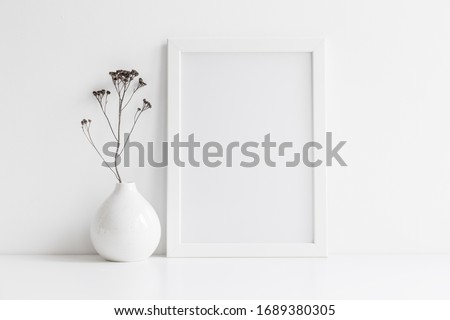 White desk with photo frame and  minimal round vase with a decorative twig against white wall.  #1689380305