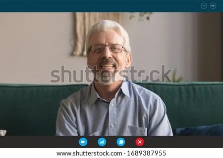 Headshot portrait screen application view of elderly grandfather sit on couch at home talk on video call with relatives, happy senior man communicate online using Webcam on modern computer gadget Royalty-Free Stock Photo #1689387955