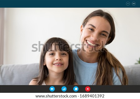 Headshot portrait of smiling young mother and little daughter speak talk on video call from home, screen view of happy mom and small girl child chat using Webcam, communicate online on quarantine Royalty-Free Stock Photo #1689401392