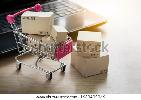 Paper shopping small box express in a shopping cart and laptop notebook on wood table background. Online shopping concept. Royalty-Free Stock Photo #1689409066