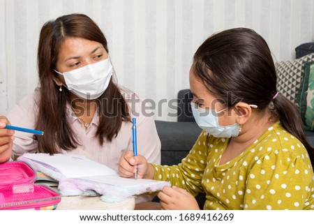 Home schooling concept image with mother and daughter studying while wearing face masks because of current corona virus threat - Current health care / education /  parenting  concept #1689416269