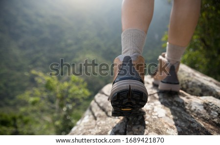 Successful hiker enjoy the view on mountain top cliff edge #1689421870