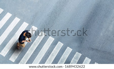 Human life in Social distance. Aerial top view with blur man with smartphone walking at pedestrian crosswalk on grey pavement street road with empty space. #1689432622
