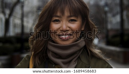 Street photographer in cozy turtleneck smiles happy to take in the smells and sights of a new city in autumn #1689458683