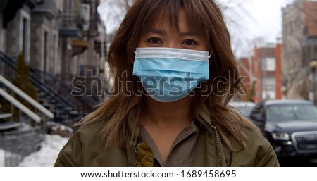 Portrait of woman wearing face mask  during coronavirus pandemic protecting herself against pathogens #1689458695