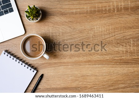 desk office with laptop, blank notepad, coffee cup and pen on wood table. Flat lay top view copy spce. Royalty-Free Stock Photo #1689463411