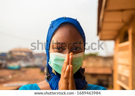 closeup of a beautiful muslim lady wearing hijab using face mask to prevent, preventing, prevented herself from the outbreak in the society and pleading that people should wear face mask #1689463984