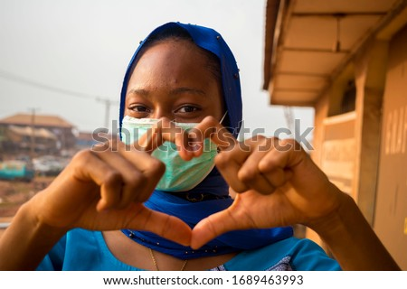 closeup of a beautiful muslim lady wearing hijab using face mask to prevent, preventing, prevented herself from the outbreak in the society and did a love sign #1689463993