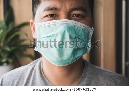 Close up young asian man wearing protection face mask against coronavirus. #1689481399