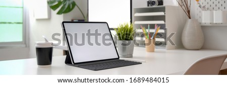 Cropped shot of portable office desk with mock-up computer devices, supplies and decorations on white table  Royalty-Free Stock Photo #1689484015