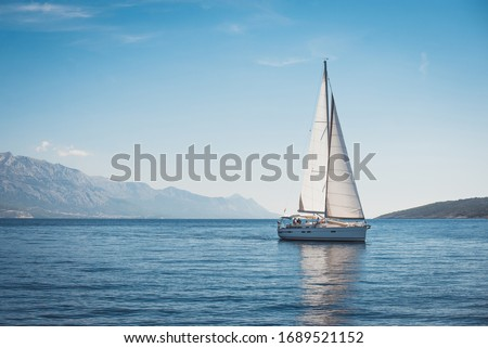 Sailing yacht in the sea against the backdrop of mountains Royalty-Free Stock Photo #1689521152