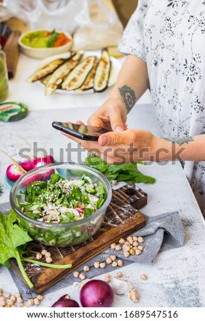 Phone picture of food. Hands make smartphone photography of summer fresh kale, cabbage salad for social media blogging. Concept for online order services. Vegan meal.