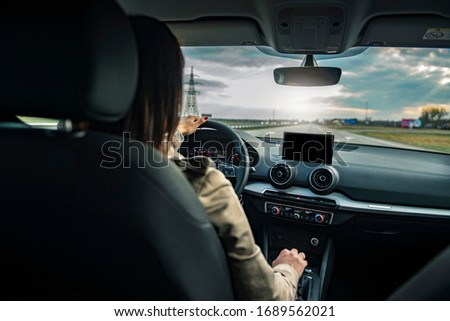 Young beautiful female driving an automobile on a highway . Royalty-Free Stock Photo #1689562021