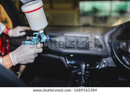 Free service for injection of the Covid-19 virus in the car. Picture of a mechanic wearing a protective mask and spraying the Covid-19 disinfectant in the car.