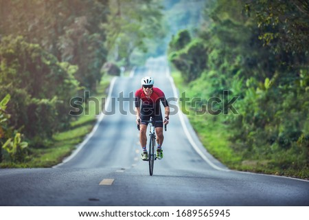 Cycling competition, cyclist athletes riding a race at high speed on mountain road, Sportsmen bikes in the morning, Royalty-Free Stock Photo #1689565945