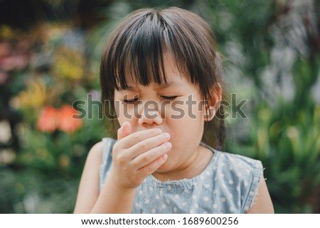 Kids using hand covering her mouth while cough which is incorrect sneezing posture. Concept of stop and prevention covid-19 or coronavirus spreading. #1689600256