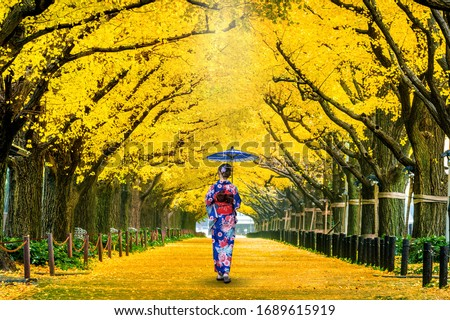 Beautiful girl wearing japanese traditional kimono at row of yellow ginkgo tree in autumn. Autumn park in Tokyo, Japan. #1689615919