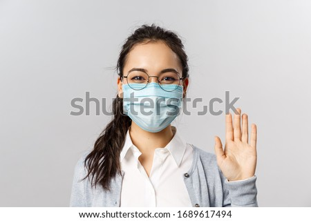 Covid19, virus, health and medicine concept. Portrait of friendly young girl in medical face mask saying hi, hello waving hand and grinning with eyes, keep safe during pandemia, quarantine #1689617494